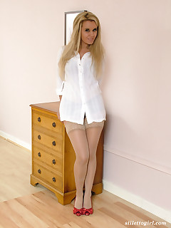 Hot blonde in her bedroom wearing red high heels and nylon stockings